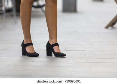 Fashionable Mary Jane shoes. Closed toe black high fashion heels with strap.  Woman's long sexy legs walking on the grey pavement downtown. Stylish leather shoes with thick heel. Retro style pumps.
