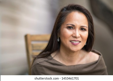 Fashionable mature Asian woman smiling.