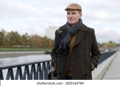Fashionable mature man wearing woolen coat and Irish flat cap walking along canal quay  bicycle during overcast autumn day