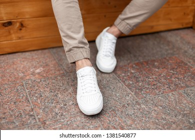 Fashionable men's white leather sneakers. Stylish men's shoes. Casual design. Close-up of male legs.