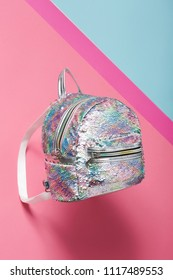 A fashionable mermaid scale backpack isolated against the bright pink and blue background. The trendy women's accessory featuring iridescent sequins, a top handle, a front pocket, a zipper closure.