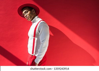 17f424fc03f fashionable mixed race man in hat and suspenders posing on red with copy  space
