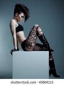 fashionable model with hairstyle sitting on the cube