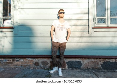 Fashionable model man with sunglasses in a white fashion T-shirt with stylish military pants and white sneakers stands near a vintage wooden wall