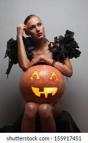 Fashionable model sitting with halloween pumpkin