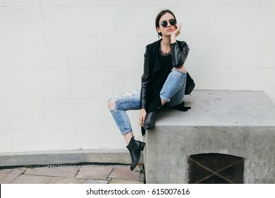 Fashionable model in sunglasses posing at the wall