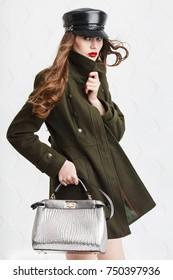 Fashionable model wearing stylish military green coat, leather cap, holding silvery bag, handbag. Young beautiful woman posing on white background. Studio portrait. Female fashion concept