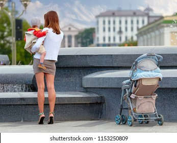 Fashionable modern mother on a city street with a pram. Young mother with a child in her arms is standing by the fountain. Attractive mother walking with a baby in a stroller, healthy lifestyle