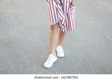 Fashionable modern young woman in a striped long pink sundress in stylish leather white sneakers walks around the city. Summer fashion. Close-up of female legs.