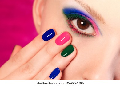 Fashionable multi-colored manicure short nails and makeup brown eyes close-up on the girl model.