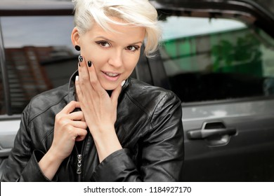 Fashionable nail design with black and white lacquer on a smiling blonde girl close - up in a leather jacket.Stylish makeup.Hair coloring platinum blonde.Nail art.