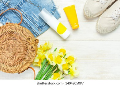 Fashionable natural organic round rattan bag, denim shorts, beige women's espadrilles, sunscreen, yellow narcissus daffodil flowers on light wooden background flat lay. Summer fashion concept Ecobags