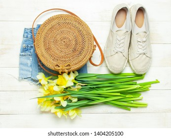 Fashionable natural organic round rattan bag, denim shorts, beige women's espadrilles, yellow narcissus daffodil flowers on light wooden background flat lay. Summer fashion concept. Ecobags from Bali