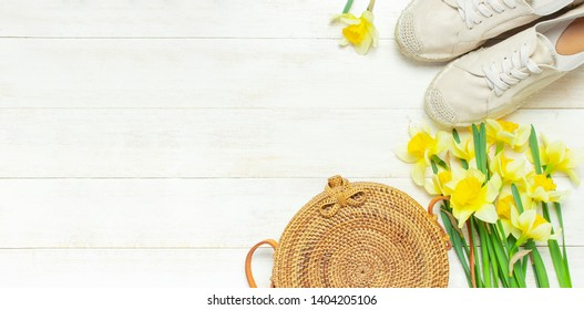Fashionable natural organic round rattan bag, beige women's espadrilles yellow narcissus daffodil flowers on light wooden background flat lay Trendy bamboo bag Ecobags from Bali Summer fashion concept