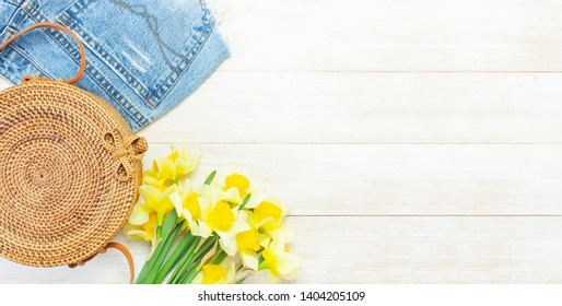 Fashionable natural organic round rattan bag, denim shorts, yellow narcissus or daffodil flowers on light wooden background flat lay Trendy bamboo bag Ecobags from Bali Summer fashion concept Top view