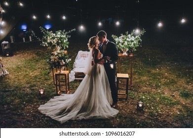 Fashionable newlyweds stand at night against the backdrop of chic decorations and flowers,electric bulbs and garlands,in the backlight. Night shooting of bride and groom.Floristics. Grain,film effect