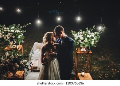 Fashionable newlyweds stand at night against the backdrop of chic decorations and flowers, electric bulbs and garlands, in the backlight.Night shooting of  bride and groom.Floristic.Grain, film effect