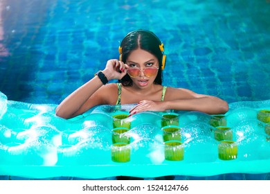 Fashionable photo: Portrait of a seductive brunette woman in sun-protected glasses, yellow headphones posing with her mouth ajar in a pool with a mattress. Summer vacation at a tropical resort