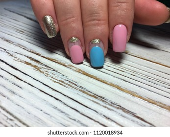 fashionable pink manicure with blue pattern and gold design on a textured background
