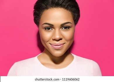 Fashionable Portrait of attractive African American young woman with perfect skin and natural make up. Beautiful brunette model. Skin and Face Care Concept. Looking on camera against pink background