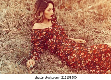 Fashionable portrait of a beautiful girl in a dress in the field
