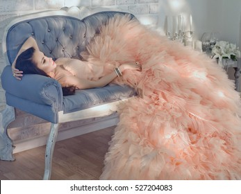 Fashionable portrait of beautiful lady in gorgeous couture dress on sofa. Couture elegant, evening dress fashion model posing. Princess in luxury gown. Holiday look. Morning of bride in sun room