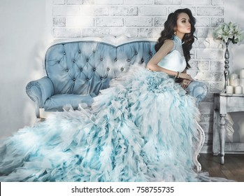 Fashionable portrait of beautiful lady in gorgeous couture dress on sofa. Holidays & Events. Evening dress. Princess dress. Christmas and New Year