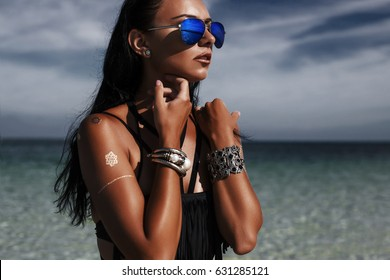 Fashionable portrait of a beautiful sexy young woman on the beach, tanned radiant skin, long healthy hair, black bikini, flash tattoo, stylish silver accessories, mirror sunglasses, low key photo
