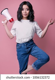 Fashionable portrait of elegant sexy asian girl in jeans and white t-shirt isolated on bright pink background