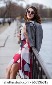 Fashionable portrait of lady with long hair in city. Image of brunette model on bright background. Young beautiful human in colorful outfit in park. Adult female person wears street style outdoors