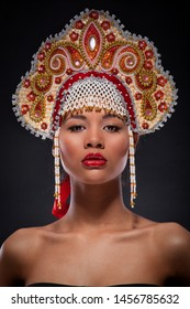 Fashionable portrait of a metis woman with the red lipstick on full lips. Studio shoot of an african american female model with the richly decorated kokoshnik on her head. Russian style, mixed culture