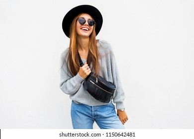 Fashionable portrait of smiling elegant brunette girl in sunglasses , black trendy hat and grey sweater posing over white wall. Bum bag. Positive mood.