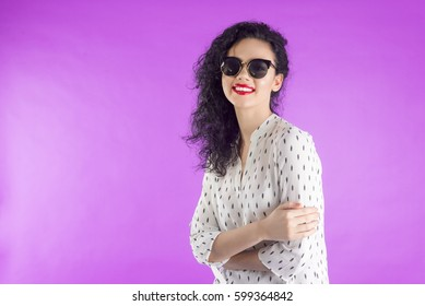 Fashionable portrait of a woman with curly hair, brunette in sunglasses on a pink background.