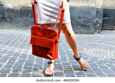 Fashionable portrait of a young short haired beautiful woman in grey sexy evening dress with red leather backpack purse.  Fashion model. Close up photo of woman hands  holding red backpack