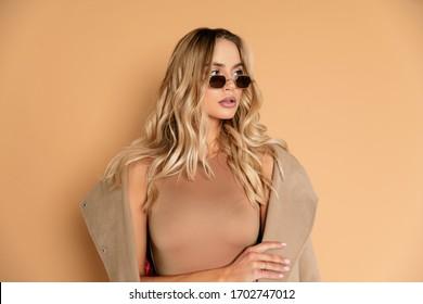 Modisches, hübsches blondes Modell, das sehr sexy mit beigem Mantel im Studio mit retuschiertem Foto ist, perfekte Haut und sehr schönes Mädchen, das für Magazin oder Hintergrund schön ist