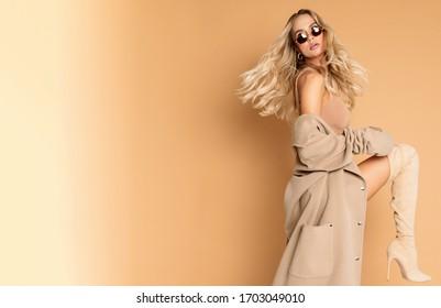 Mohionfähiges, hübsches blondes Modell, das sehr sexy mit beigefarbenem Mantel im Studio, retuschiges Foto perfekte Haut und sehr schönes Mädchen nett für Magazin beschnitten am besten geeignet für Werbung