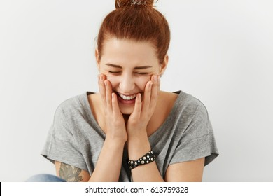 Fashionable pretty girl with hair knot and tattoo dressed in stylish grey t-shirt holding hands on cheeks and closing eyes, feeling embarassed, smiling shyly and joyfully sitting at blank studio wall