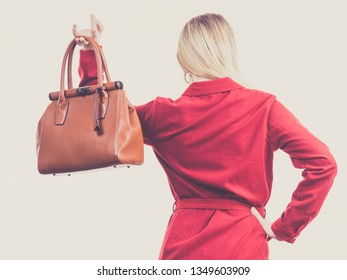 Fashionable pretty young woman wearing elegant casual red short dress and holding leather bag presenting stylish outfit.