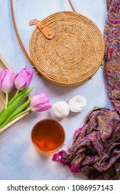 Fashionable rattan bag, cup of tea, tulips and scarf on light background. Copy space, top view