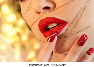 Fashionable red makeup and manicure with gold threads. Glamor beauty. Nail art. Sensual lips.