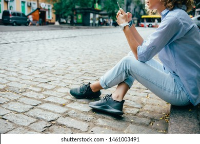 Fashionable relaxed young woman sitting on sidewalk near road using smart phone. Female traveler wearing blue shirt, jeans and sneakers resting in city browsing internet on mobile device.