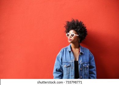 Fashionable retro style girl standing in front of a red wall