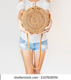 Fashionable round female bag made of natural rattan material in the hands of a young girl against a light wall. Rattan handbag, ecobags from Bali. Eco-bag concept, trendy bamboo bag.