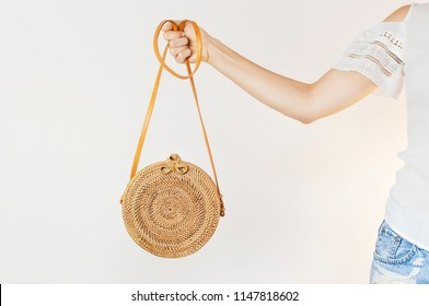 Fashionable round female bag made of natural rattan material in the hands of a young girl against a light wall. Rattan handbag, ecobags from Bali. Eco-bag concept, trendy bamboo bag. Copy space