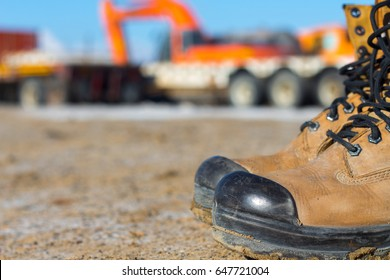 Fashionable safety brown boots on work area with construction equipment background