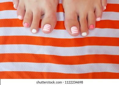 Fashionable sea design a nogtiya standing, on a striped orange background. Summer pedicure