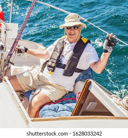 Fashionable senior fisherman in a hat and breeches looking at the camera.A senior citizen is wearing a life jacket.