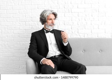 Fashionable senior man sitting on sofa near white brick wall