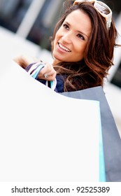 Fashionable shopping woman holding bags and smiling