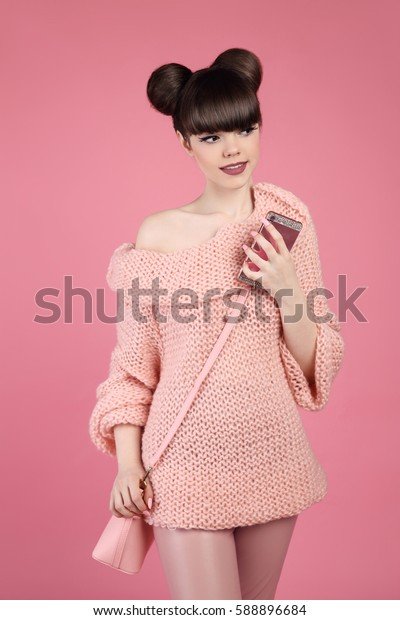 Fashionable smiling teen girl portrait. Young brunette wears in wool sweater with handbag holding mobile phone, posing over isolated on pink background.